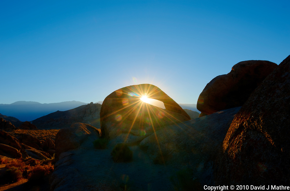 Sunrise Starburst Through Mobius Arch in the Alabama Hills near Lone Pine, California. Composite of 5 images taken with a Nikon D3x and 14-24 mm f/2.8 lens (ISO 100, 24 mm, f/22, 1/15 to 1/250 sec) processed using Photomatix Pro.