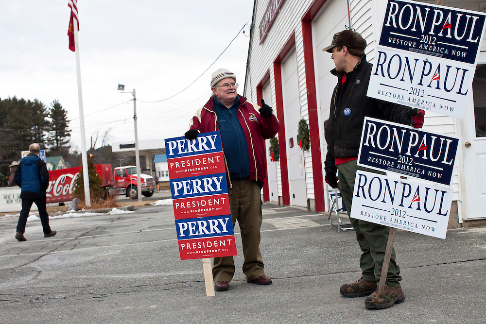Dan Fleetham, with Perry signs, and Philip Salvail, right, campaign for their preferred candidates outside the Canaan Fire Station on Tuesday, January 10, 2012 in Canaan, NH. Brendan Hoffman for the New York Times