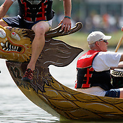 SHOT 7/29/2007 - A flag catcher sits atop the head of a dragon boat as the team returns to the docks during the 2007 Colorado Dragon Boat Festival. The flag catcher has to stay in the boat for the run to qualify. The sport of Dragon boat racing is over 2000 years old and features teams of 18 paddlers - nine men and nine women plus someone to steer the boat - all rowing in sync to the beat of a drum and racing to a flag 200 meters away on Sloan's Lake in Denver, Co. Founded in 2001 to celebrate Denver?s rich Asian Pacific American culture, the Colorado Dragon Boat Festival has become the region?s fastest growing and most acclaimed new festival. Festival-goers get to explore the Asian culture through demonstrations, crafts, shopping, eating, and the growing sport of dragon boat racing. .(Photo by Marc Piscotty / © 2007)