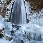 """After several days of below-freezing temperatures, Wahkeena Falls is surrounded by ice. Wahkeena Falls is located in Oregon's Columbia River Gorge and drops 242 feet (74 meters) in several tiers. Wahkeena means """"most beautiful"""" in Yakama Indian."""