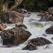 The Merced River flows past large granite rocks in a narrow gorge at the western side of Yosemite National Park, California.