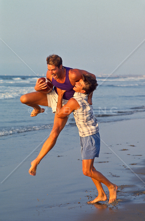 Two men playing a casual game of football on the beach in Santa Monica, CA