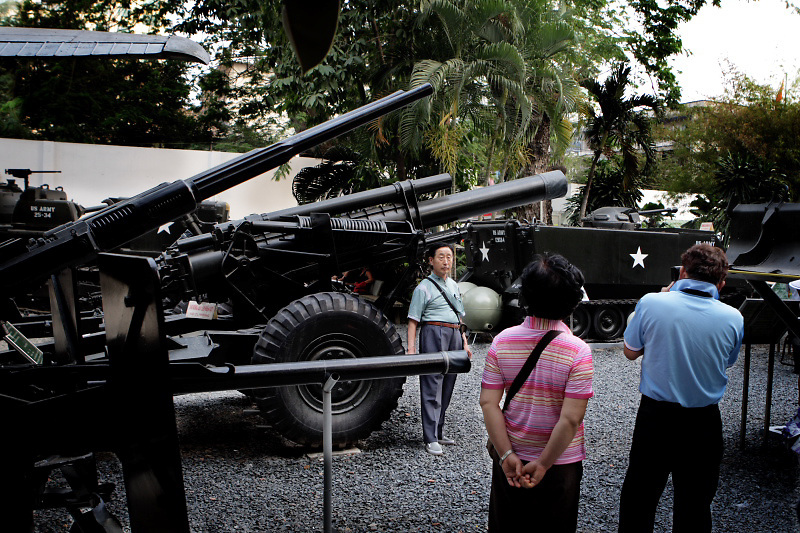 A veteran soldier is standing in the War Remnants Museum. His family member is taking pictures among military equipment located within a walled yard.  National Liberation Front or Vietcong,  was an army based in South Vietnam that fought the United States and South Vietnamese governments during the Vietnam War (1959-75).
