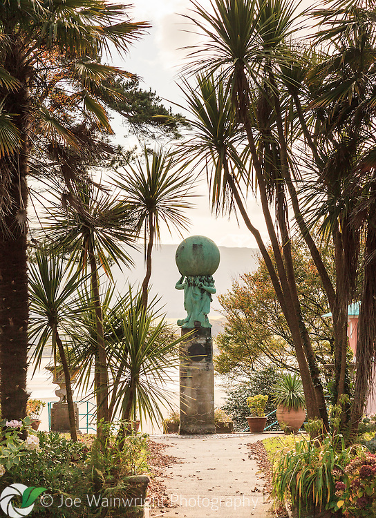 Plantings of Cordyline australis around the Statue of Hercules provide an exotic effect at Portmeirion, Gwynedd, North Wales.