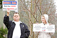 Jennifer Drake glances over at Michael Sheneman as they stand next to each other Wednesday at a Recall CdA rally as the two display opposite opinions of movement to recall the Coeur d'Alene mayor and half the city council.
