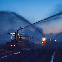 On the outskirts of Miami, water trucks irrigate farm areas in the pre-dawn hours.