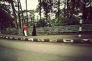 A woman in a burqa walks behind her husband on the street in Kuala Lumpur, Malaysia, Southeast Asia,