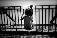 Unaccompanied, destitute boy, who has not bathed for a very long time, hangs from rail on Howrah Bridge, Calcutta (Kolikata), India.
