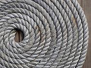 A coil of rope waits on a dock in Kladeshölmen, Sweden.