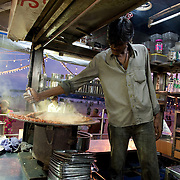 A vendor at a street food stall on Chowpati beach in Mumbai prepares Pao Bhaji, a favorite mumbai snack.