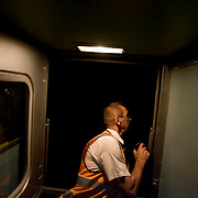 The Ghan.  Roman Krasowski, assistant train conductor, communicating with the drivers for a scheduled stop at Tennant Creek to allow a freight train to pass.  Tennant Creek, Northern Territory, Australia. Image © Arsineh Houspian/Falcon Photo Agency.