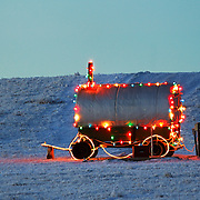 A shepherd's Wagon is lighted for Christmas north of Kaycee, Wyoming.  The blue od the sky at dusk reflects on the snow, making the image feel as cold as it was.  Temperature was below zero. New Year's Day, 2005.
