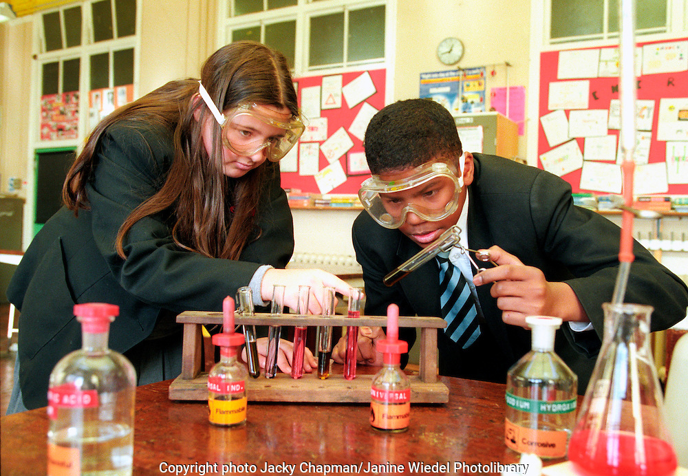 Secondary school pupils working on science experiments in classroom laboratories.