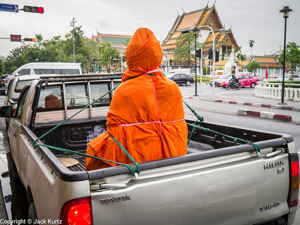 "12 NOVEMBER 2012 - BANGKOK, THAILAND:   A Buddha statue wrapped in saffron cloth before being delivered to a store on Bamrung Muang Street. Bamrung Muang Street in Bangkok. Thanon Bamrung Muang (Thanon is Thai for Road or Street) is Bangkok's ""Street of Many Buddhas."" Like many ancient cities, Bangkok was once a city of artisan's neighborhoods and Bamrung Muang Road, near Bangkok's present day city hall, was once the street where all the country's Buddha statues were made. Now they made in factories on the edge of Bangkok, but Bamrung Muang Road is still where the statues are sold. Once an elephant trail, it was one of the first streets paved in Bangkok. It is the largest center of Buddhist supplies in Thailand. Not just statues but also monk's robes, candles, alms bowls, and pre-configured alms baskets are for sale along both sides of the street.    PHOTO BY JACK KURTZ"