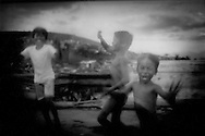 """Squatter boys run along side of taxi in front of the original Smoky Mountain landfill where rotting garbage would spontaneously catch fire and send up plumes of smoke in the Tondo slum of Manila, Philippines.  Families made a meagre living collecting, cleaning and selling recyclable materials.  Now families live in similar fashion at the """"New"""" Smoky Mountain nearby."""