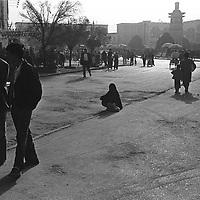 KASHGAR, 20 SEPTEMBER 2001: a veiled beggar woman sits on a street near the mosque in Kashgar. .(photo by: katharina hesse/Grazia Neri).