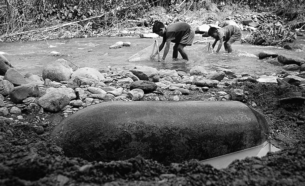 Children fishing near a large bomb exposed on the banks of a stream at the base of their village.