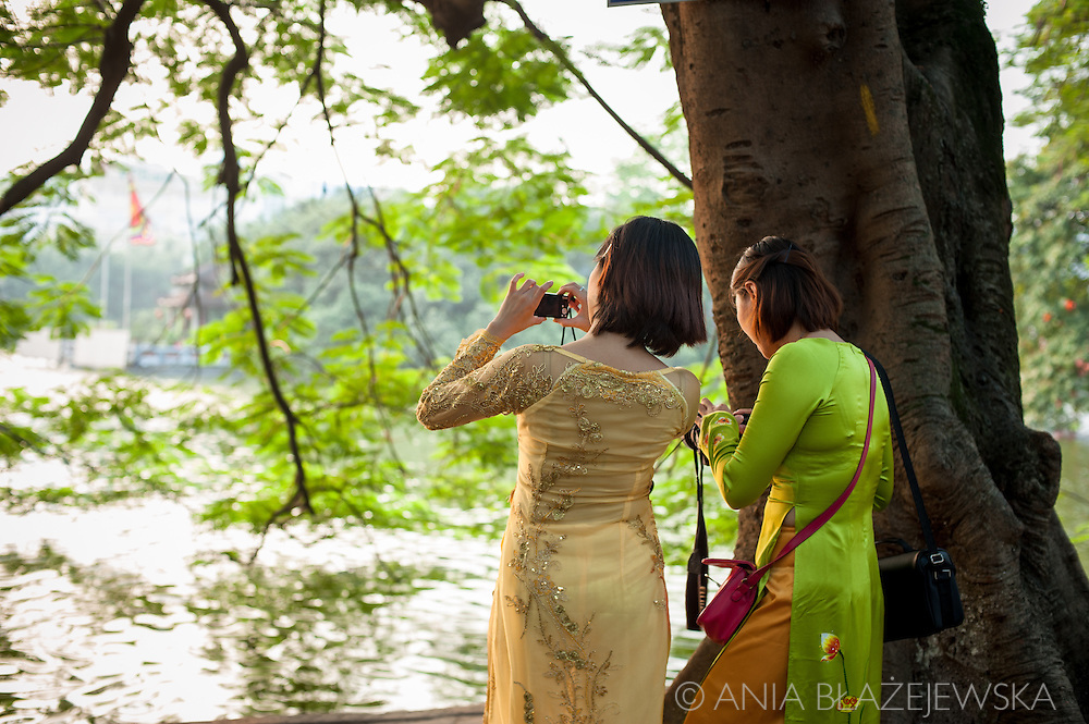 Vietnam, Hanoi. Two women who wear traditional ao dai, take photos at Hoan Kiem Lake.