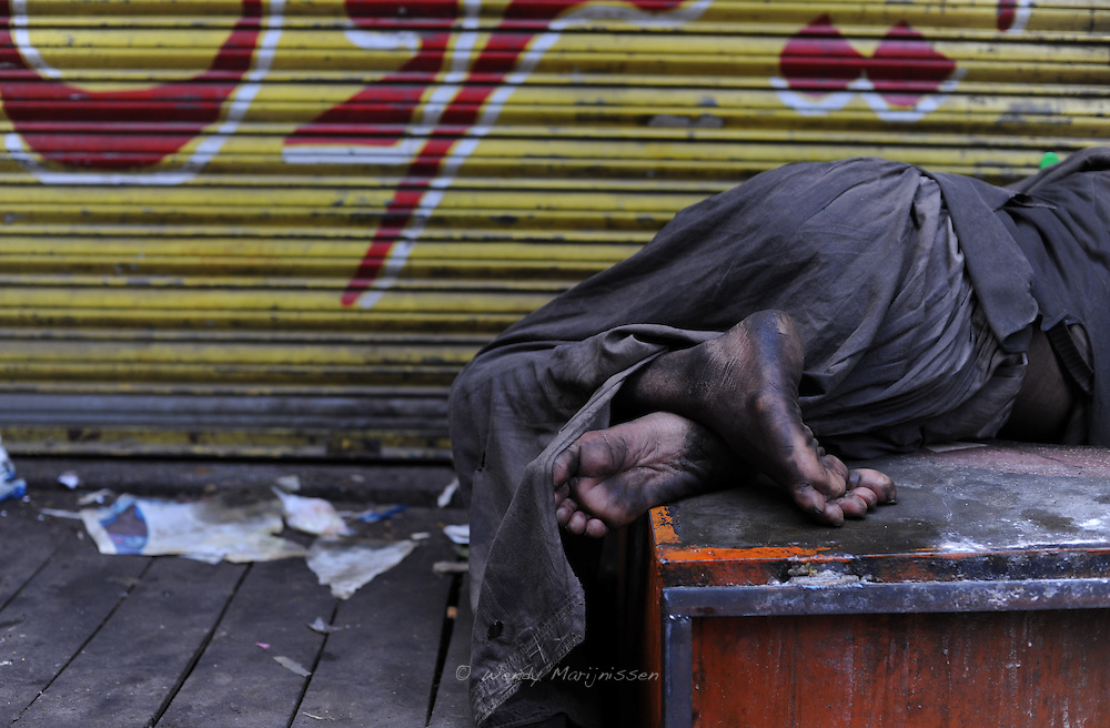 A homeless man is sleeping outside a shop in the old city of Lahore. Pakistan, 2009