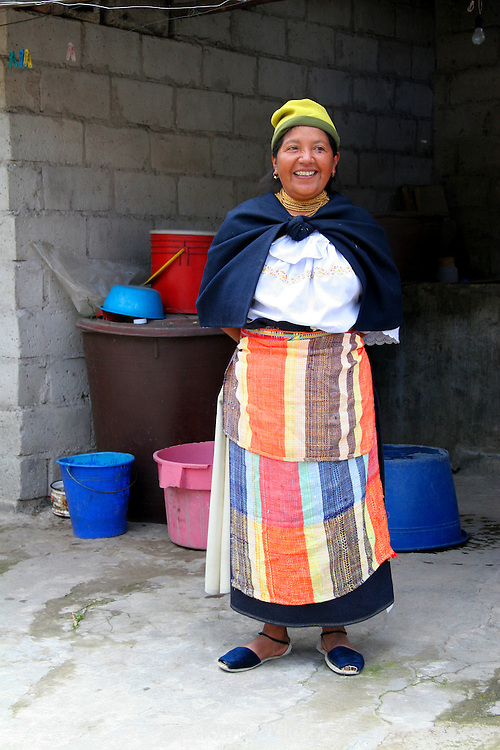 South America, Ecuador, Peguche. An Ecuadorian woman welcomes visitors to see her home in Peguche.