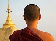Buddhist monk and gold encrusted pagoda spire. Kyaiktiyo Pagoda, the Golden Rock, Myanmar