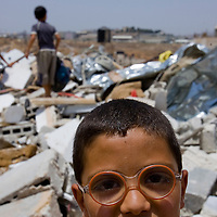 A Palestinian boy stands near the ruins of a home that was razed in East Jerusalem's Beit Hanina neighbourhood July 13, 2010. Israel razed on Tuesday an inhabited Palestinian home in East Jerusalem for the first time in eight months, effectively ending an unofficial freeze of such internationally-condemned demolitions. Israel's Jerusalem municipality said the home was built without a city permit Photo by Olivier Fitoussi