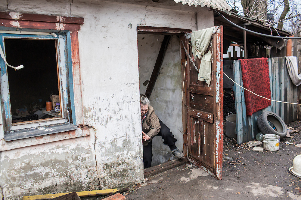 Alla Kozikova, 81, climbs out of the basement shelter in which she and some of her neighbors have been living for days on February 3, 2015 in the Petrovsky district of Donetsk, Ukraine. The neighborhood has been under heavy shelling for the past four days, and a brief pause allowed a few residents to leave their basement hiding places for some fresh air.