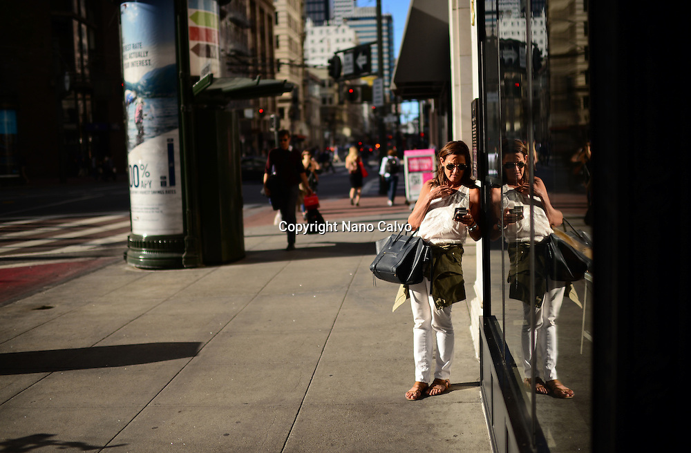 Woman using smartphone in street, San Francisco.
