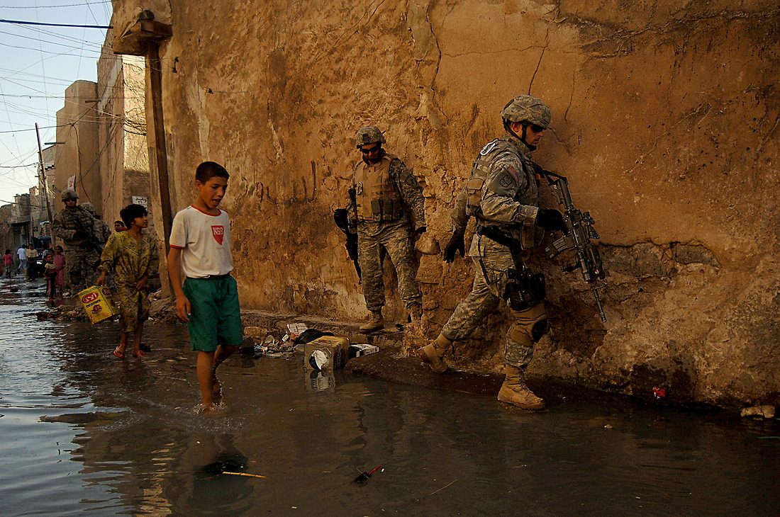 Soldiers from 2nd Platoon Charlie Company 1/17th Infantry 172nd Stryker BDE Ft. Wainwright, Alaska, try and navigate their way through a sewage flooded street June 13, 2006 during a foot patrol in the neighborhood of Shek Fahai, Mosul, Iraq. — © TSgt Jeremy Lock/