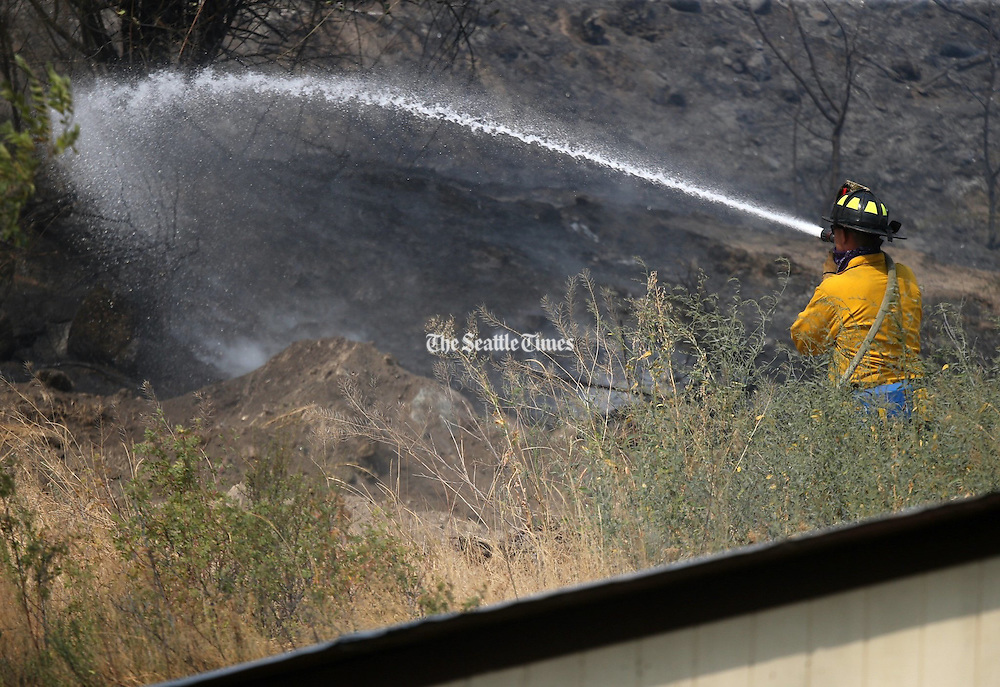 Firefighters work to stop the spread of the fire eastward towards homes and orchards near Conconully Road at Douglas Road in Okanogan Friday August 21, 2015.<br />