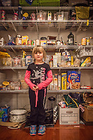 Five year old Mya Shuler organizes the pantry at her home in Martinez, California
