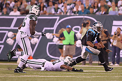 Aug 26, 2012; East Rutherford, NJ, USA; Carolina Panthers quarterback Cam Newton (1) eludes a tackle by New York Jets linebacker Aaron Maybin (51) during the first half at MetLife Stadium.