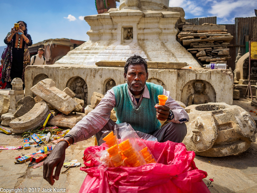 04 MARCH 2017 - KATHMANDU, NEPAL: An ice cream cone vendor sits in front of a damaged stupa at Swayambhu Stupa. The stupa was badly damaged in the 2015 Nepal earthquake. Recovery seems to have barely begun nearly two years after the earthquake of 25 April 2015 that devastated Nepal. In some villages in the Kathmandu valley workers are working by hand to remove ruble and dig out destroyed buildings. About 9,000 people were killed and another 22,000 injured by the earthquake. The epicenter of the earthquake was east of the Gorka district.     PHOTO BY JACK KURTZ