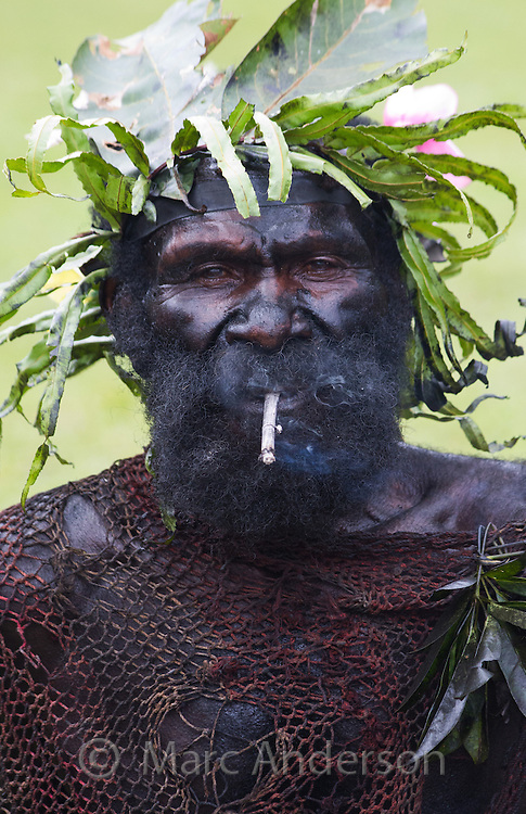 Portrait of a man smoking and dressed in traditional tribal outfit for the Goroka Show, an annual festival in the Papua New Guinea Highlands