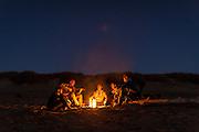 Friends play guitar around a campfire on South Beach, near Newport Oregon.