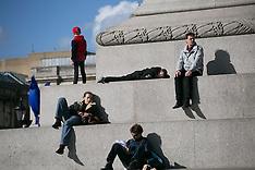 FEB 26 2014 Tourists get a sunbath at Trafalgar Square.
