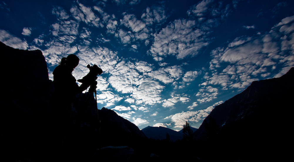 Silhouette of a videographer against a backdrop of mountains and clouds