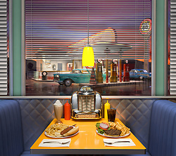 Hamburger and hotdot shot on the table at a retro American diner looking with a vintage gas station in the background