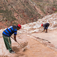 Peru, Maras, Father and son working among salt evaporation pools of Salineras in Sacred Valley in the Andes mountains