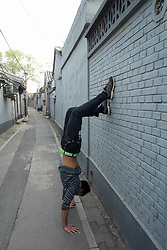 Chinese teenage boy doing handstand in a historic lane or hutong in Beijing China