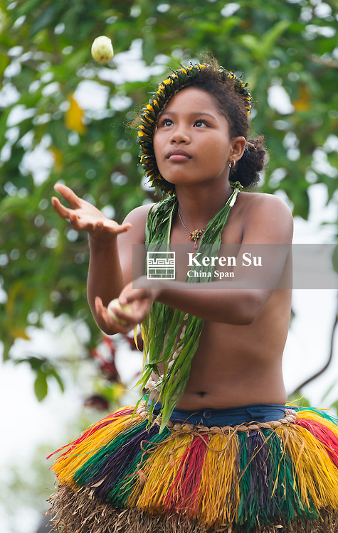 Yapese girl in traditional clothing juggling fruit at Yap Day Festival, Yap Island, Federated States of Micronesia