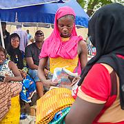 LÉGENDE: Rosine prépare en train de préparer un emballage pour une cliente qui a acheté ses poissons. LIEU: Marché de Chagoua, N'Djaména, Tchad. PERSONNE(S): Rosine Remadsi au centre de la photo, le client à la droite de la photo. En arrière plan d'autres vendeuses assisent et ambiance du marché.