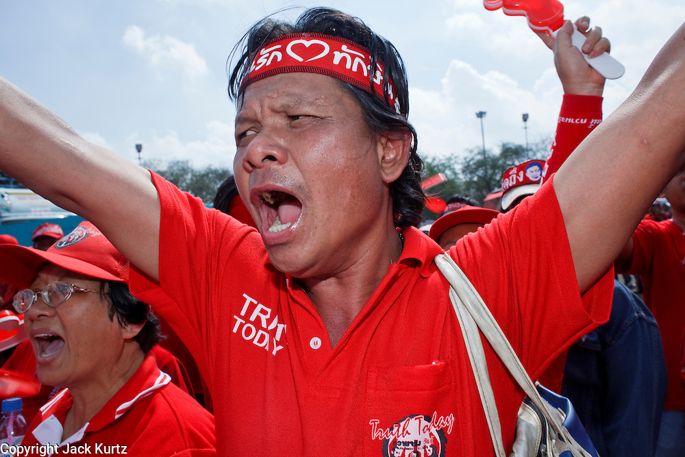 "Mar. 26, 2009 -- BANGKOK, THAILAND: An anti-government protestor cheers for the opposition during a Red Shirt rally in Bangkok Thursday. More than 30,000 members of the United Front of Democracy Against Dictatorship (UDD), also known as the ""Red Shirts""  and their supporters descended on central Bangkok Thursday to protest against and demand the resignation of current Thai Prime Minister Abhisit Vejjajiva and his government. Abhisit was not at Government House Thursday. The protest is a continuation of protests the Red Shirts have been holding across Thailand in March.  Photo by Jack Kurtz"