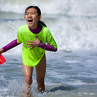 NAPLES, FL -- March 13, 2010 -- Bethany Latham, 9, of Bethlehem, Pennsylvania, laugh as she gets hit with the surf as she collects clams on the beach during the Nature's Wonders program at The Ritz-Carlton in Naples, Fla., on Saturday, March 13, 2010.  The three hour programs let kids experience a more involved, educational nature program while parents get free time to enjoy themselves sans kids.