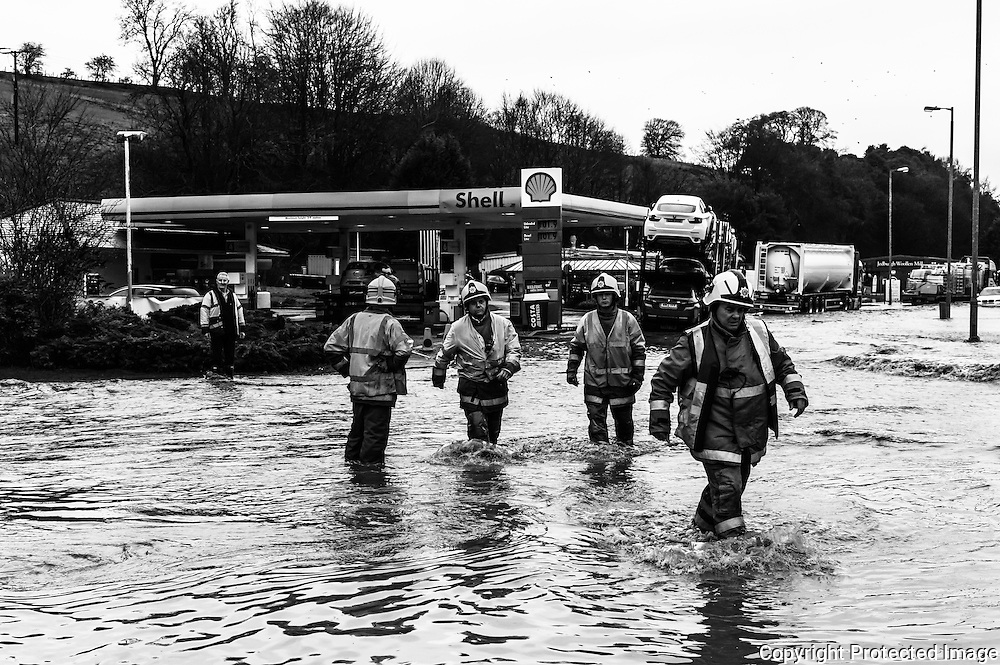 Jedburgh, Scottish Borders, UK. 27th January 2016. Firecrews wade through a flooded A68 road in Jedburgh. The area recieved intense torrential rainfall on Wednesday morning.