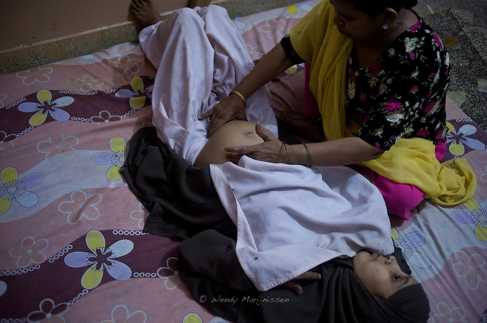 Fatima checks the position of the baby on her 7 month pregnant client. Fatima Kaniz, became a dai after her husband died and has been assisting deliveries for over 20 years. She learned the trade from working in the labour room in a private hospital and saw it as a good source of income.  Karachi, Pakistan, 2011