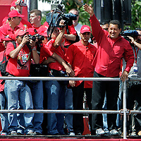 Venezuelan President Hugo Chavez waves to millions of people filling the streets of downtown Caracas, Sunday, November 26, 2006.