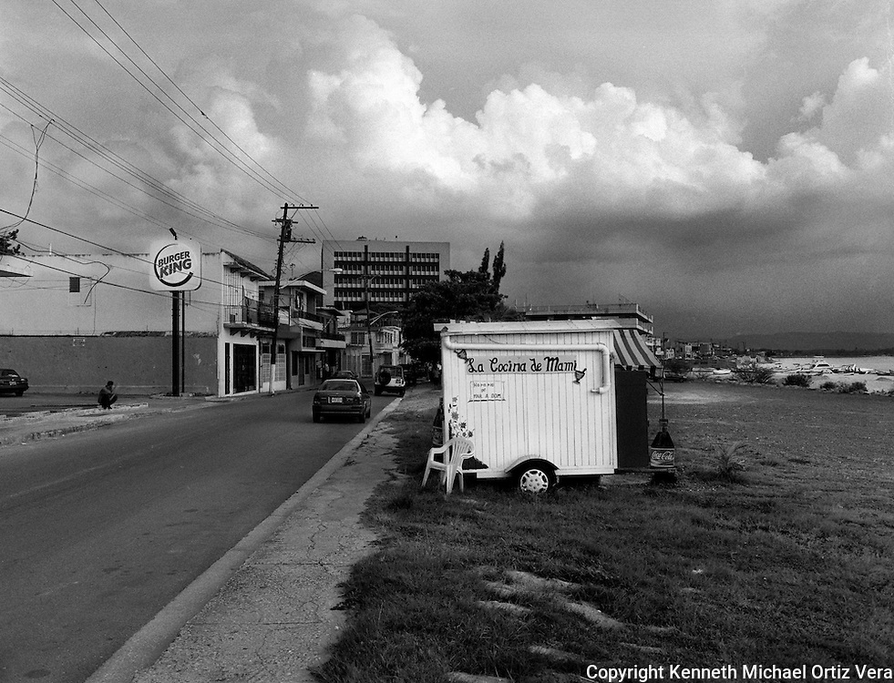 La cocina de Mami is a small kiosk food business in the town of Aguadilla Puerto Rico.  The Kiosk was closed for the day due to the on-coming storm in the distance.