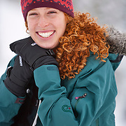 Erica Koltunuk, a young red-headed woman returns to the parking lot carrying her board following a day of riding in the backcountry of Alta Utah.