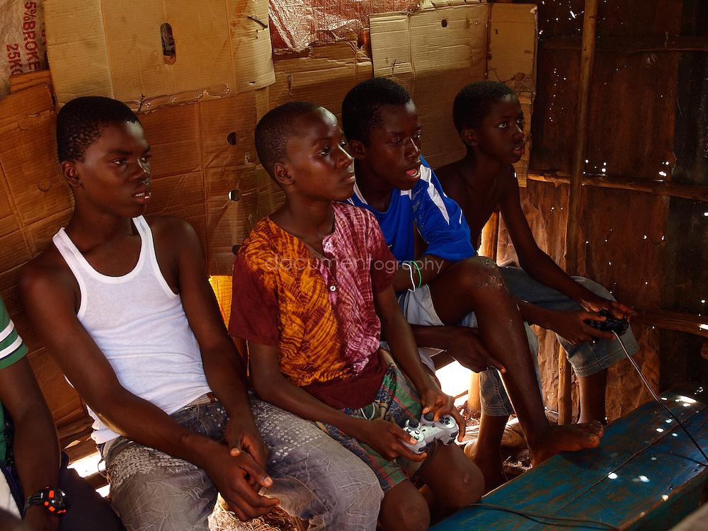 Boys play football at a local Playstation centre, Kroo Bay, Freetown, Sierra Leone